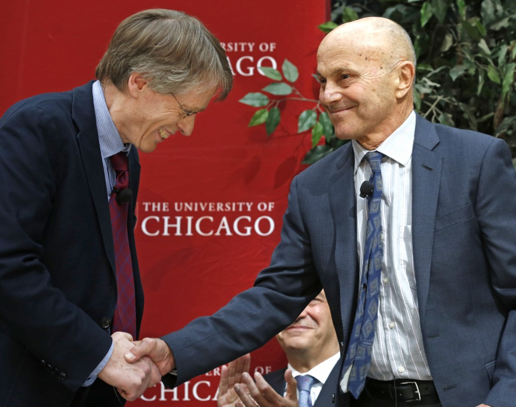 Nobel Prize winners Lars Peter Hansen, 60, left, and Eugene Fama, 74, of the University of Chicago, shake hands at a news conference Monday, Oct. 14, 2013, in Chicago after being named two of the three winners of the Nobel prize for economics. They share the prize with Robert Shiller, 67, of Yale University.