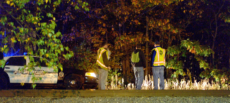 Investigators survey the scene of a fatal accident along train tracks between Forest Avenue and Irving Street in Portland on Wednesday night. A man who was walking along the tracks was struck and killed by a freight train.