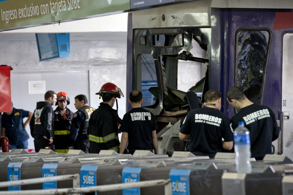 Police and firemen work on a commuter train that slammed into the end of the line when arriving to Once central station in Buenos Aires, Argentina, on Saturday. Emergency officials said at least 80 people are injured, five seriously. Security Secretary Sergio Berni says they are still evacuating the wrecked train and have found no fatalities.