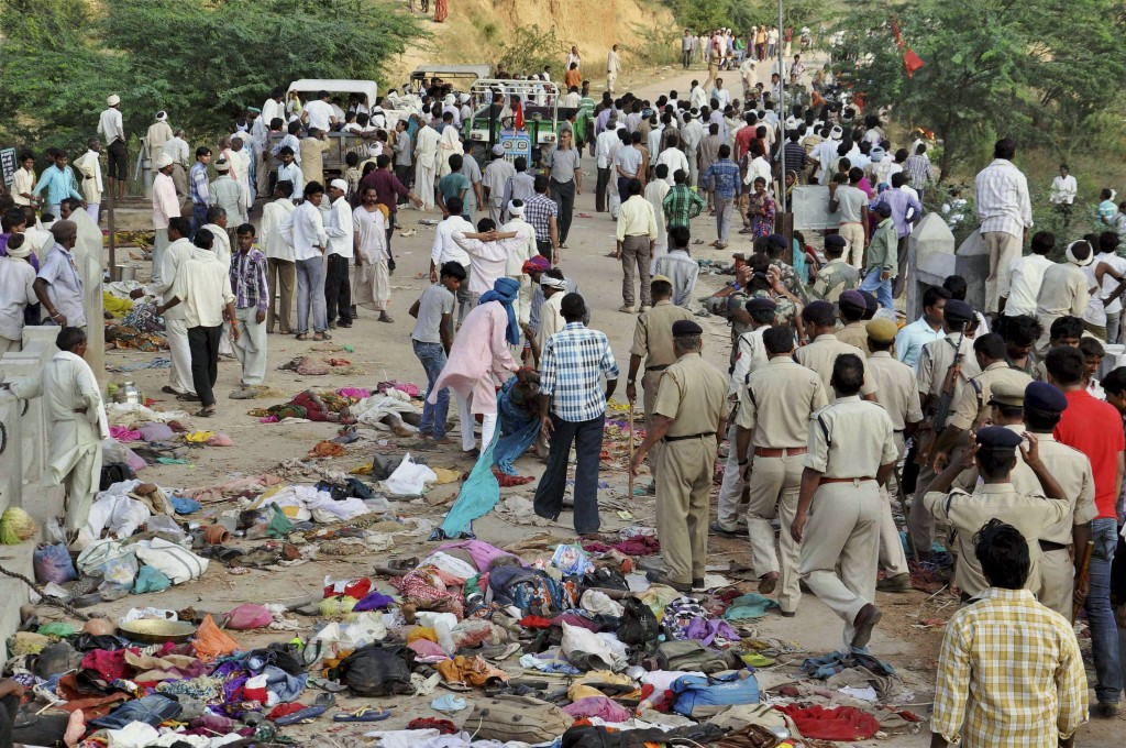 In this Sunday, Oct. 13, 2013 photo, Indian villagers gather as policemen, in uniform, arrive at the scene of a deadly stampede on a bridge across the Sindh River in Datia district in Madhya Pradesh state, India. Pilgrims visiting a temple for a popular Hindu festival in India stampeded on fears a bridge would collapse, and more than 100 people were crushed to death or died in the river below, officials said Monday. Scores more were injured, and some bodies may have washed away. (AP Photo)