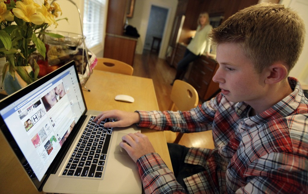 Mark Risinger, 16, checks his Facebook page on his computer as his mother, Amy Risinger, looks on at their home in Glenview, Ill. An influential pediatricians' group says unrestricted media use has been linked with violence, cyberbullying, school woes, obesity, lack of sleep and a host of other problems.