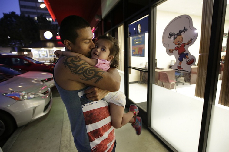 Carlos Rodriguez kisses his 2-year-old daughter, Diana, who relies on the Special Supplemental Nutrition Program for Women, Infants and Children while waiting for his wife outside a WIC offic, in Los Angeles.