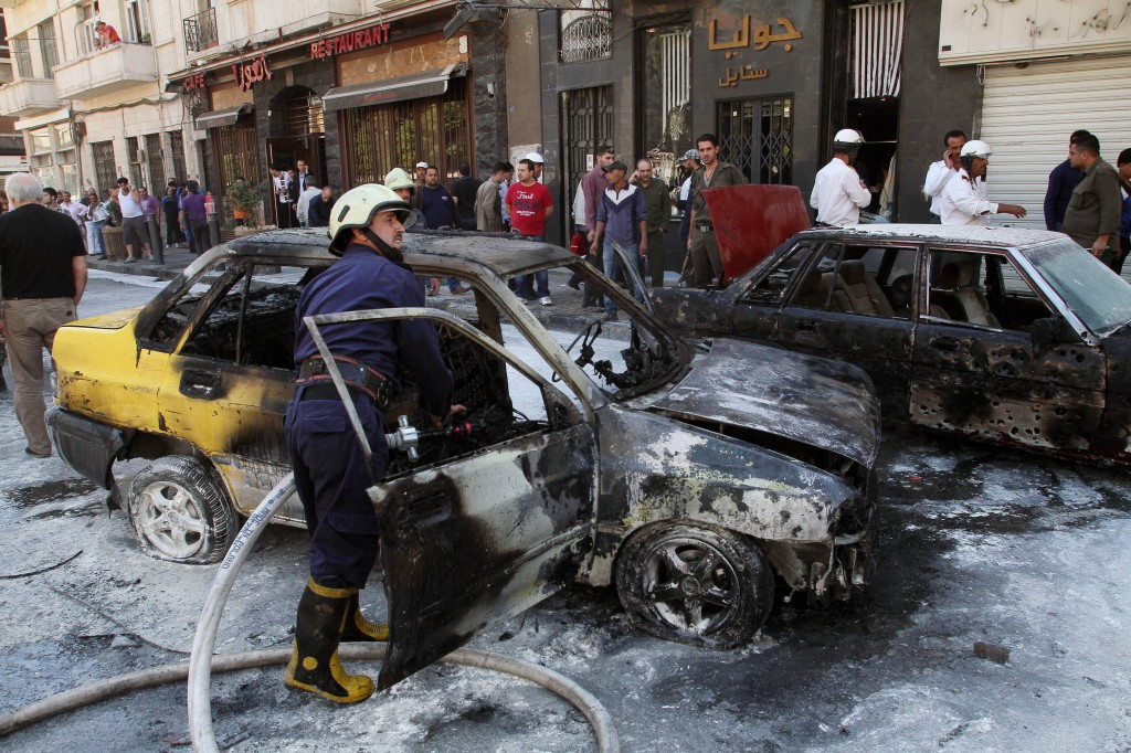 Firefighters extinguish a burning vehicle after two mortar rounds struck the Abu Roumaneh area in Damascus, Syria, on Saturda. Syria's state news agency said two mortar rounds struck an upscale neighborhood in the Syrian capital of Damascus, killing at least one child and injuring a dozen people.