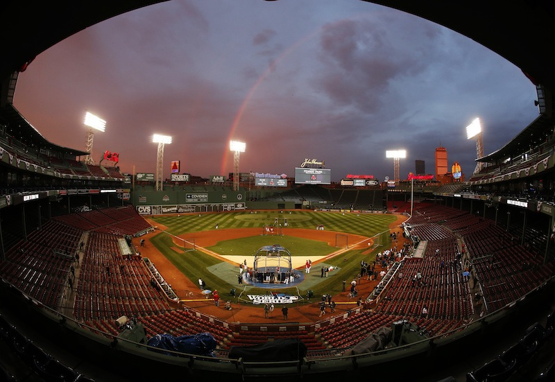 In this file image taken with a fisheye lens, Boston Red Sox players take batting practice as a rainbow appears in the sky above Fenway Park on Tuesday, Oct. 22, 2013, in Boston. An average ticket to Fenway Park for Game 6 on Wednesday has hit $2,374, making it the most expensive in history. MLB