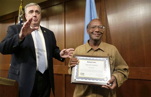 Glen James, of Boston, right, holds a special citation while facing reporters with Boston Police Commissioner Edward Davis, left, during a news conference at police headquarters, in Boston, Monday, Sept. 16, 2013. James, who is homeless, turned in a backpack containing $2,400 in U.S. currency, almost $40,000 in traveler's checks, as well as Chinese passports and other personal papers to police after finding the items in a Boston mall Sept. 14. (AP Photo/Steven Senne)