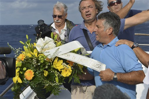 "Fishing boat captain Calosero Spalma, right, today throws a wreath, with writing on a ribbon written in Italian, ""Fishermen of Lampedusa,"" into the sea to pay tribute to the victims of Thursday's migrant shipwreck off the coast of the southern Italian island of Lampedusa. A 20-meter boat packed with migrants sank Thursday when the ship capsized after they started a fire to attract attention. Just 155 people survived, 111 bodies have been recovered and more than 200 are still missing."