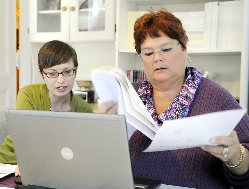 Emily Brostek, left, assists Charlene Brousseau with enrolling in an Affordable Care Act insurance exchange today at Brostek's office in Augusta. Online enrollments have encountered delays, but people wishing to to enroll can telephone or fill out paper forms.