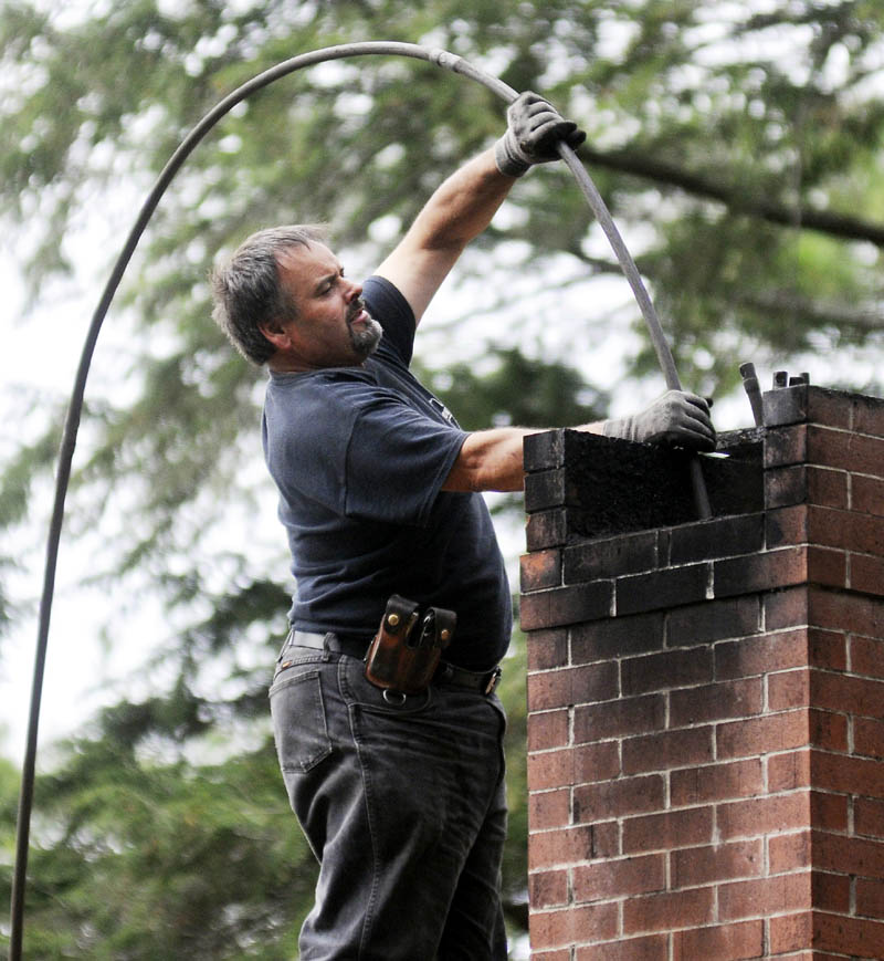 SWEEP: Dave Pelletier of Downeast Chimney sweeps a flume on a home in Litchfield on Wednesday October 23, 2013.