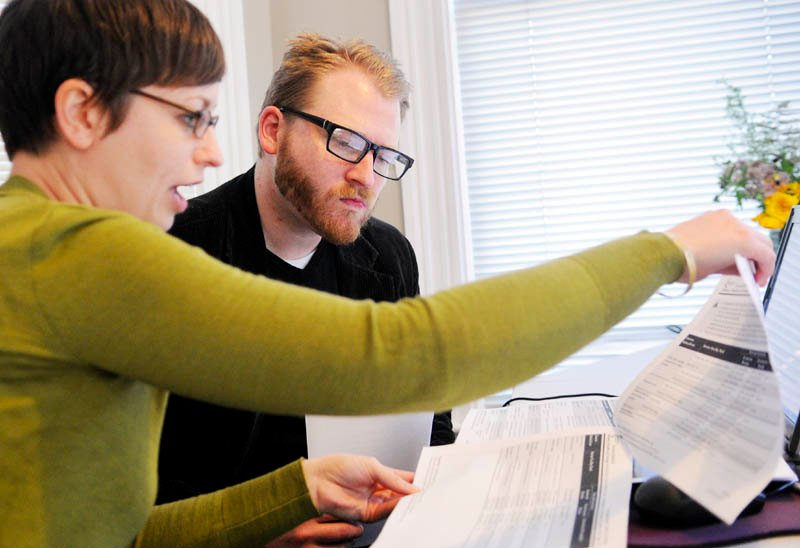 Emily Brostek, left, assists Jesse Miller, of Portland, learn about health insurance options under the Affordable Care Act today. Brostek works at the Consumers for Affordable Health Care office in Augusta.
