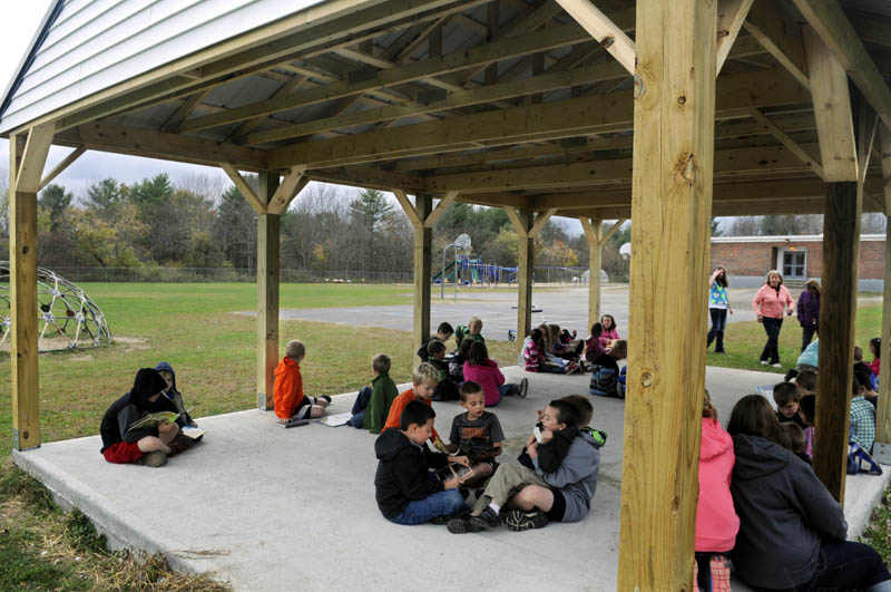Pittston Consolidated School students read to each other Tuesday under the new outside classroom. Third graders read books to kindergarten students in the structure.
