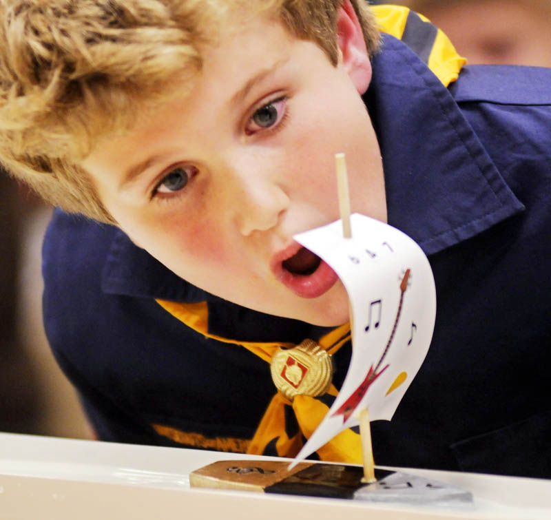 Wolf Scout Ben Nathan, 7, of Hallowell blows his sailboat Thursday during Raingutter Regatta that Cub Scout Pack 6 held in Farmingdale. Over 20 scouts from Hallowell and Farmingdale competed in races with the balsa wood vessels they constructed with six inch masts during the event. Powered by blowing the sail, winners were determined by which boat arrived at the end of a rain gutter first.