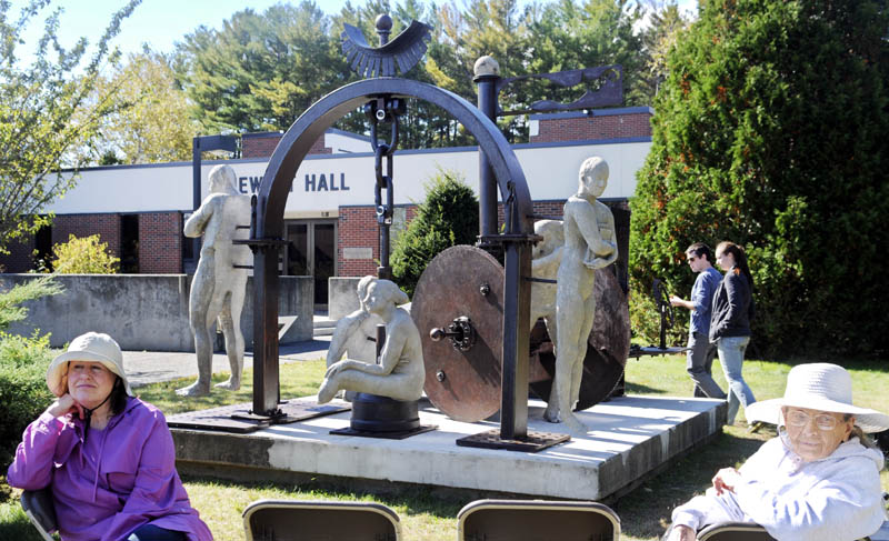 """People gather around a sculpture Tuesday outside of Jewett Hall at the University of Maine in Augusta following a dedication ceremony for the piece titled """"Imperfection is the Greatness of Man."""" Students devoted five months to creating the sculpture, which was relocated from the Viles Arboretum to its new permanent location on the campus green."""