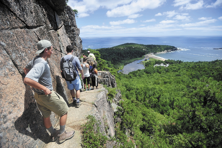 A line of hikers files up the Beehive Trail near Sand Beach at Acadia National Park in Bar Harbor in July. The park may need to close at the height of the fall foliage season if congress can't reach a deal on federal spending.