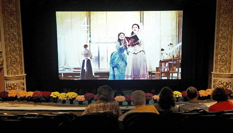 """People sit in the balcony of the Waterville Opera House as a scene from Tchaikovsky's """"Eugene Onegin"""" flashes on the screen, with a countdown to showtime, before a live satellite simulcast of The Metropolitan Opera performance today."""
