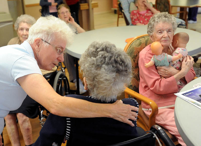 Barbara McCutcheon, left, a recreation assistant at Oak Grove Center in Waterville, speaks with resident Mary Getchell during activity time Friday.