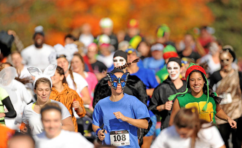 Nearly 200 costume wearing runners make their way down Mayflower Hill Road at Colby College in the Freaky 5K Fun Run organized by Hardy Girls Healthy Women today. The fun run was created to help draw girls away from the scantily clad costumes and toward the scary and creative costume designs.