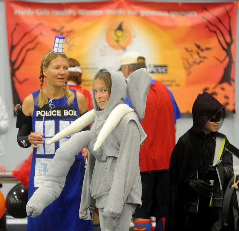 "Alison Stabins, 11, center, dressed as an elephant as her mother Amy, left, dressed as Tardis from ""Dr. Who,"" wait for the start of the Freaky 5K Fun Run organized by Hardy Girls Healthy Women at the Colby College field house today."