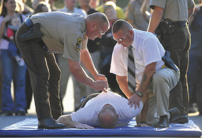 Lt. David Rackliffe, left, pulls a barb from the back of Franklin County Sheriff Scott Nichols as he is supported by Lt. David St. Laurent, right, after being shocked with a stun gun by Chief Deputy Steven Lowel during an open house on Wednesday.