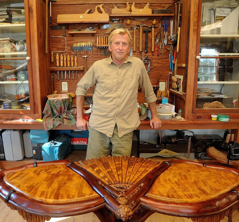 Randy Holden, of Norridgewock, stands in his workshop next to a table he just finished. Holden recently won an award for best artist in woodworking at the Jackson Hole Fall Arts Festival. Holden's business, Elegantly Twisted Rustic Furniture, creates unique furniture using the existing curves and characteristics of the natural wood.
