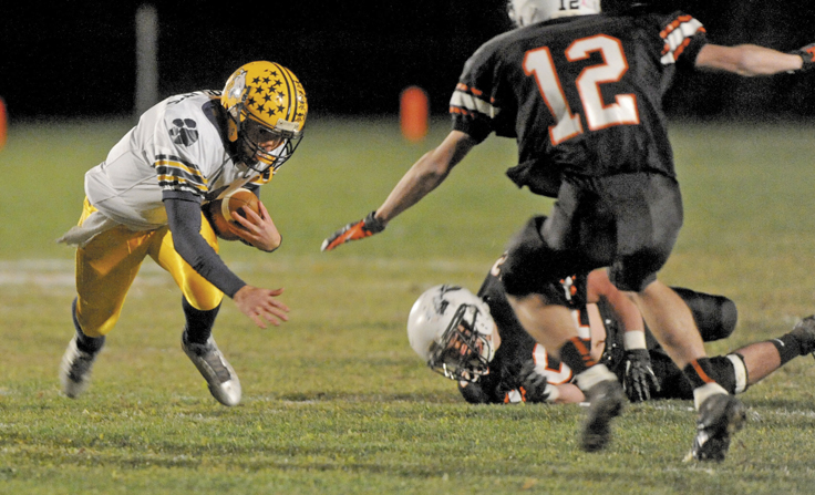 Mt. Blue quarterback Andrew Pratt gets tripped up by Skowhegan's Gus Benson, 52, in the first quarter of the Cougars' 42-40 win Friday night in Skowhegan.