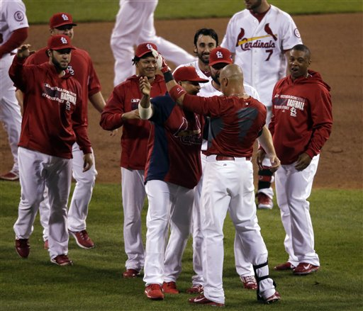 St. Louis Cardinals' Carlos Beltran is congratulated by teammates after his game-winning hit during the 13th inning of Game 1 of the National League baseball championship series against the Los Angeles Dodgers Saturday, Oct. 12, 2013, in St. Louis. (AP Photo/Chris Carlson)