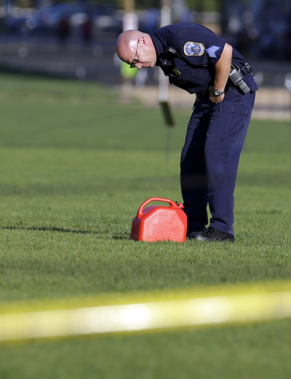 A police officer looks at a container at the scene on the National Mall in Washington, where, according to a fire official, a man set himself on fire Friday, Oct. 4, 2013. The official said the man was flown by helicopter to a hospital. (AP Photo/Alex Brandon)
