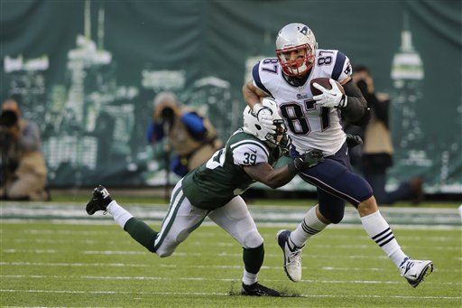 New York Jets' Antonio Allen (39) tackles New England Patriots' Rob Gronkowski during overtime Sunday in East Rutherford, N.J. The Jets won the game 30-27.