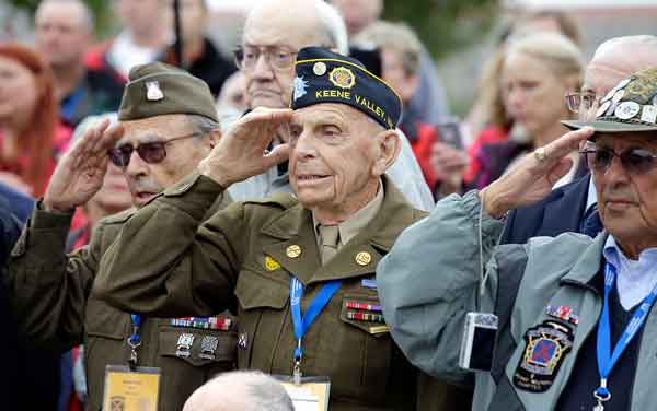 World War II 10th Mountain Division veteran, Charles W. Smith, center, from Plattsburgh, N.Y., salutes with others, during the singing of the National Anthem at the WWII Memorial on Sunday in Washington.
