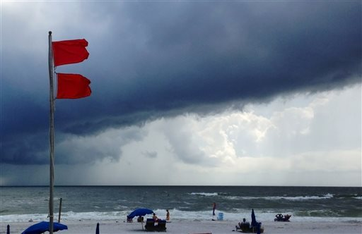 Red flags warn swimmers to stay out of the Gulf of Mexico as a squall from Tropical Storm Karen moves offshore at Gulf Shores, Ala., today. The beaches remained open, but authorities said dangerous underwater rip currents made the waters too dangerous to enter.
