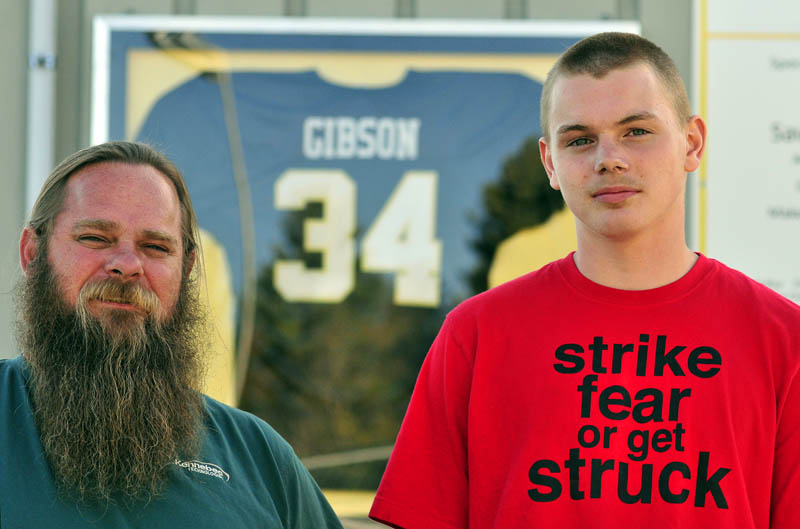 Rick and Jake Gibson stand in front of Ricky Gibson's football jersey on Wednesday at the Ricky GIbson Field of Dreams in Readfield. The field is named after Ricky, Rick's son and Jake's brother. Jake is a sophomore on the Maranacook football team this fall.