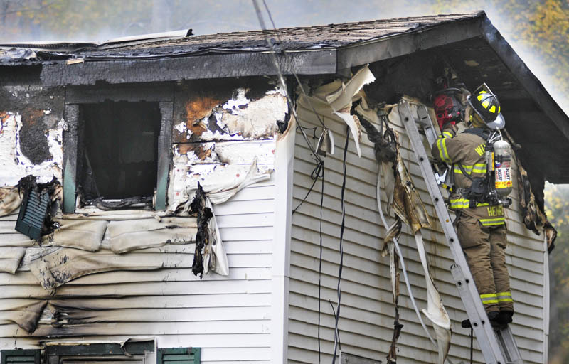Firefighters cut a ventilation hole while crews work at 119 Granite Hill Road today in Manchester.