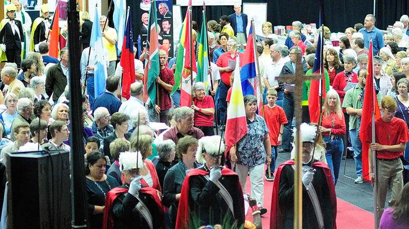 """Flagbearers march during the entrance procession for the opening mass of """"The Great Commission: One Family in Mission"""" event today at the Augusta Civic Center. The featured speaker was scheduled to be Mario St. Francis, a motivational speaker and lay Catholic evangelist."""