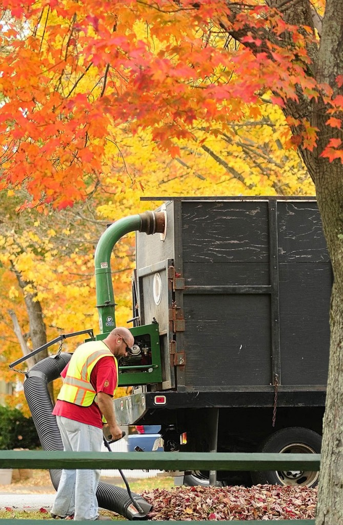 Daniel Robideau vacuums up leaves on Tuesday around the perimeter of the Gardiner Common in Gardiner. He and another city employee who was driving the truck had earlier used leaf blowers to clean off the Common and make windrows of leaves along the curb. Robideau said that they'd probably have to do it a few more times this season.
