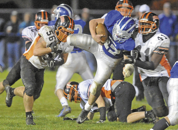 Lawrence fullback Beau Grenier, 27, gets tackled by Brunswick defenders Jacob Duffy, left, and Josh Mays, 41 in the second quarter Friday night in Fairfield.