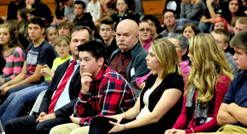 Al Althenn, center, of China, looks at Nokomis Regional High School student Katie Manzo, at right of Althenn, as she asks questions during a break in hearings at the Newport school with Justices of the Maine Supreme Court on Tuesday.
