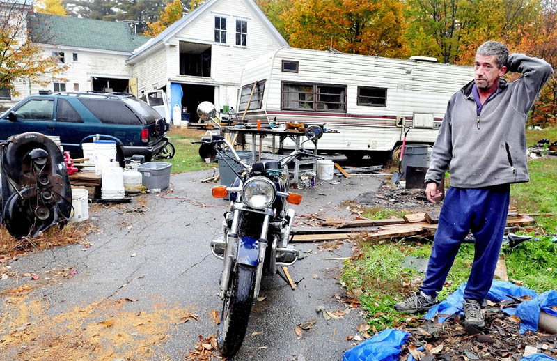 Homeowner Duane Pollis speaks outside his home on Adams Street in Wilton on Monday. Town officials say the home, numerous vehicles and piles of salvaged building materials violates a town ordinance. Wilton is imposing a $100 per day fine until the home is compliance.