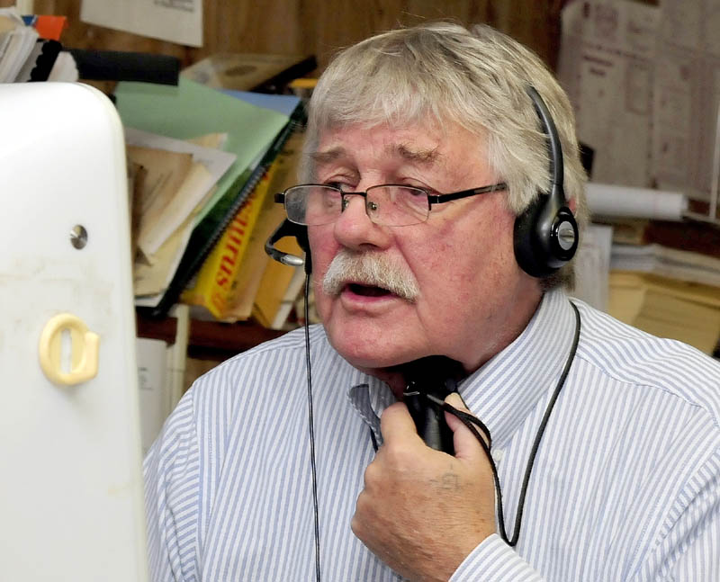 Morning Sentinel reporter Doug Harlow speaks with a subject on the phone while using an electro larynx battery-powered voicebox device.