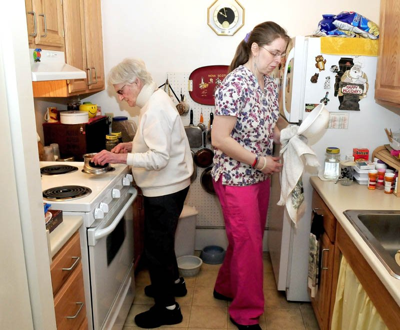 Seton Village resident Marie Rouleau, left, and Personal Support Specialist Zandra Luce work in the kitchen preparing a meal on March 25. Rouleau was among those on a waiting list for the Meals on Wheels program, which restored full service on Tuesday, according to program officials.