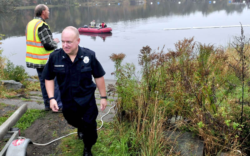 Pittsfield police officer Jeff Vanadestine walks back to his cruiser as firefighters search the Sebasticook River for debris and collect oils after a vehicle struck a nearby pole and went into the water on Monday. Vanadestine was one of the first at the scene and jumped into the water to rescue the female driver.