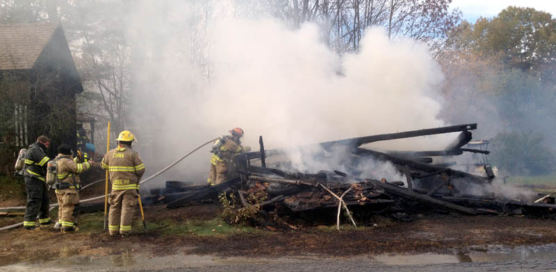 Firefighters from area departments extinguish a building fire that is considered suspicious on the South Reynolds Road in Winslow on Wednesday.