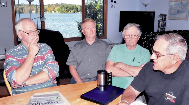 With China Lake seen in the background, these China residents expressed concern over the costs to the public if the former Cabins lakefront property is developed into the China Community Park. Pictured are, from left, Scott Adams, Scott Croker, Herb Tyler and Sheldon Bumps.