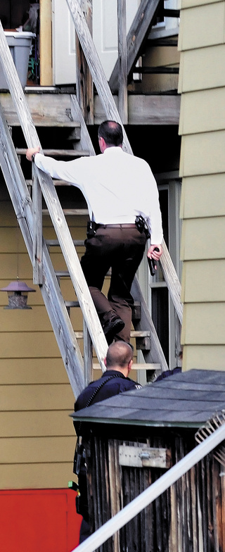 Detective David Caron, with his gun drawn, and other officers enter the second floor apartment at 90 Elm Street in Waterville on Wednesday.