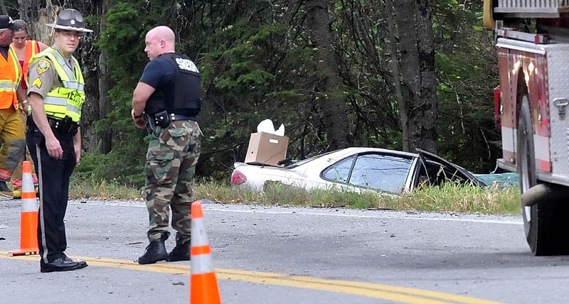 Kennebec Sheriff Office Sgt. Frank Hatch, left, surveys the scene of a two-vehicle fatal accident on Route 139 in Unity Township on Monday. A 59-year-old woman died in the Chevrolet Cavalier, background, after it collided with a pickup truck driving in the opposite direction, according to Hatch.