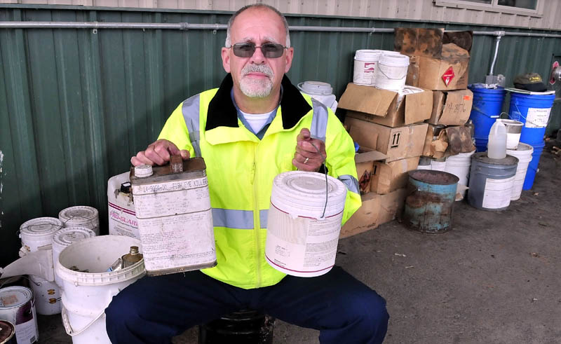 Winslow Public Works Director Paul Fongemie holds unwanted containers of liquids that are among some of the items that can be dropped off for disposal at the town garage on Halifax Street this Saturday.