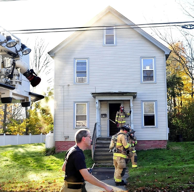 Firefighters fight a stubborn and smokey fire at a home on Oak Street in Waterville on Wednesday.