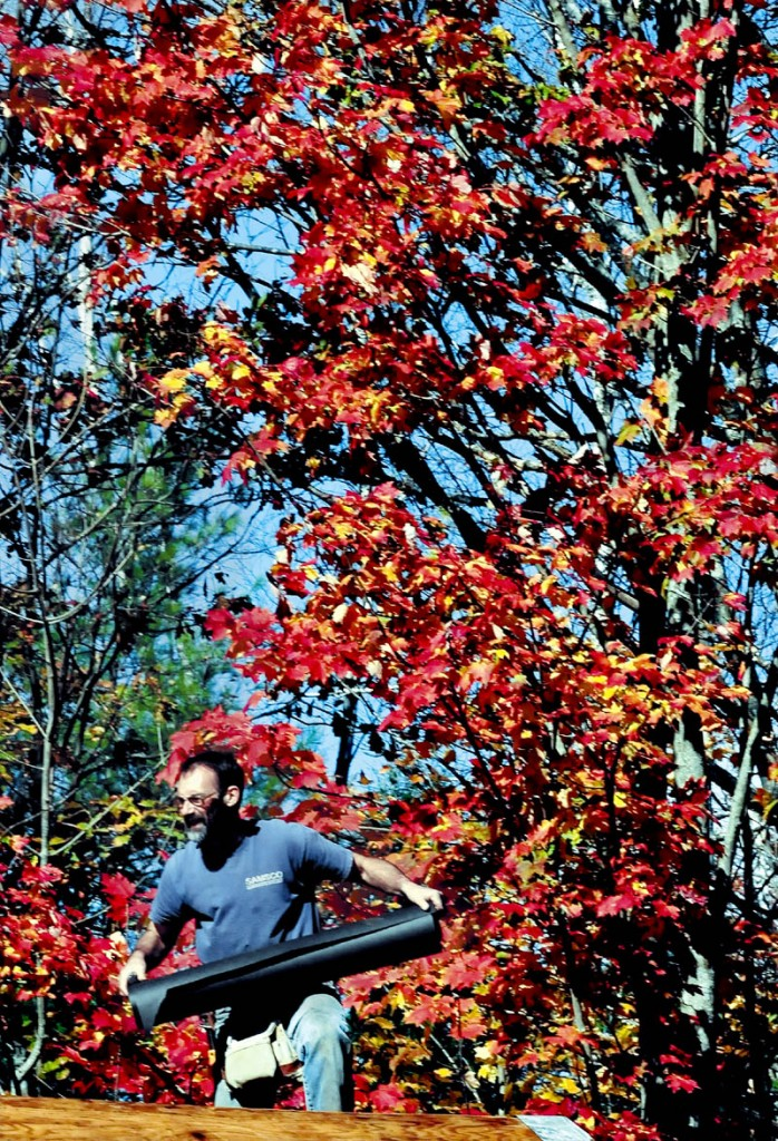 Working under a colorful maple tree, Ken Landry moves a roll of roofing material while he and others re-shingled a home in Belgrade on Sunday.