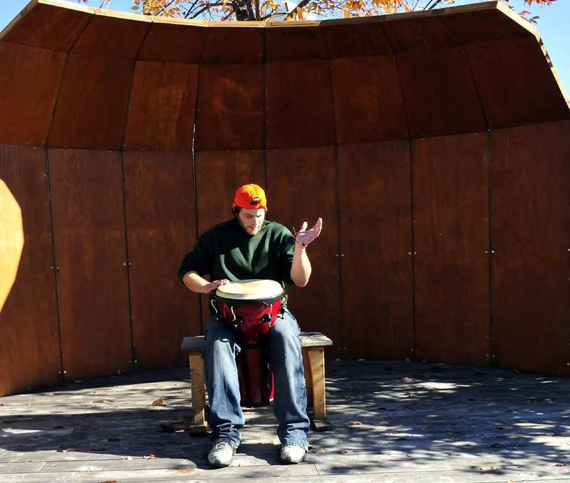 """Lucas Lovejoy plays the djembe drum inside the stage at the park in the Concourse in Waterville on Tuesday. Lovejoy said the music sounded good as it bounced off nearby building walls. """"It's real cool,"""" Lovejoy said."""