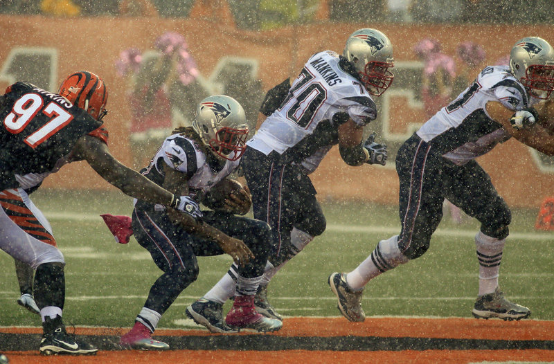Brandon Bolden has a hard time gaining traction on a fourth-quarter run in the pouring rain against a tenacious Cincinnati defense Sunday.