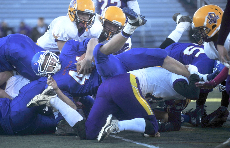 CLASS D FOOTBALL:Oak Hill High School's Kyle Flaherty, 44, dives over the pile of Bucksport High School defenders for a second quarter touchdown in the Class D state championship game at Fitzpatrick Stadium in Portland on Saturday.