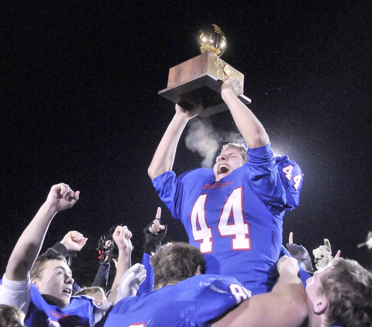 CLASS D FOOTBALL:Oak Hill High School's Kyle Flaherty, 44, hoists the championship trophy over his head as his teammates put him on their shoulders after defeating Bucksport High School 42-35 in the Class D state championship game at Fitzpatrick Stadium in Portland on Saturday.